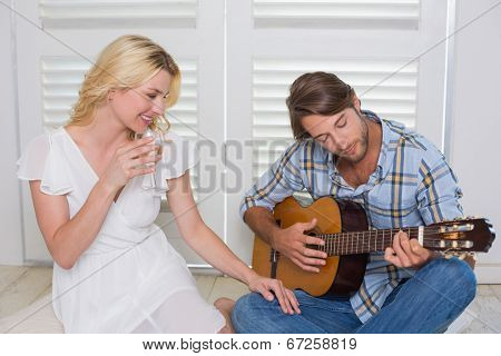 Handsome man serenading his girlfriend with guitar at home in the living room