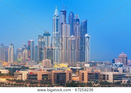 DUBAI, UAE - MARCH 31: Skyscrapers of Dubai Marina at night on March 31, 2014, UAE. Dubai Marina is a district in Dubai with artificial canal city who accommodates more than 120,000 people.