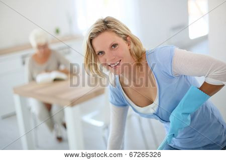 Young housekeeper cleaning floor in senior home