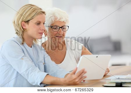 Homehelp with elderly woman using digital tablet