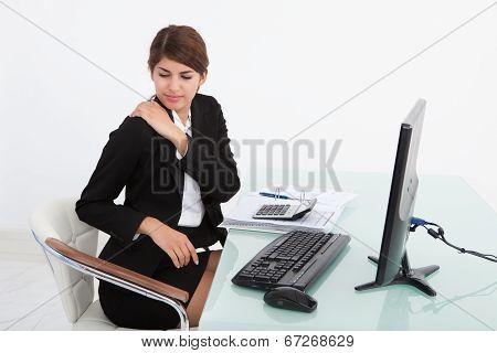 Businesswoman Having Shoulder Pain At Computer Desk