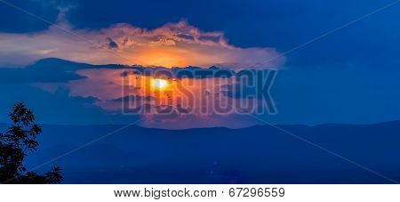 Orange Sunset Sky And Clouds Over Mountain Valley