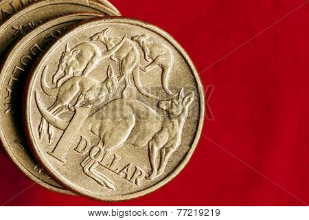 Australian money.  One dollar coins over red background.  Overhead view.