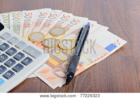 Calculator and money on the wooden table poster