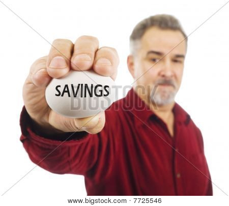 Mature Man Holds A Nest Egg With 'Savings' On It.