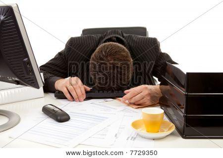 Businessman Lies With Head On Desk