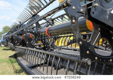 Closeup Of Harvesting Machinery While Working The Field.