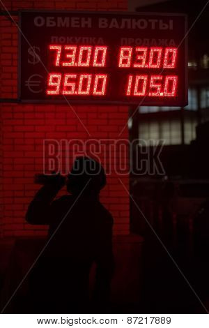 Silhouette of drinking man near board with exchange rates, Moscow, Russia. Text on board: Currency exchange, buy, sell