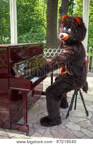 actor dressed as bear entertains playing piano on the bandstand in the park
