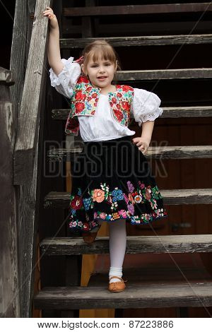 Little Girl In Traditional Costume On The Stairs