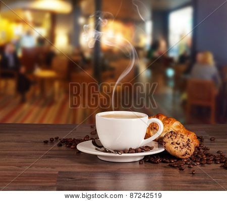 Coffee drink served with croissant on wooden table with blur cafeteria as background