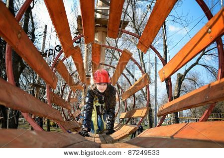 Smiling Teen Girl Crawling In A Round Wooden Maze In The Park In Spring