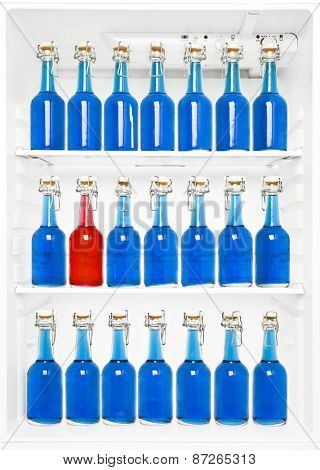 One Red Bottle among a large group of blue bottles in a fridge