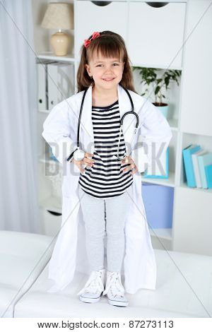 Little girl in doctor costume with stethoscope on office interior background