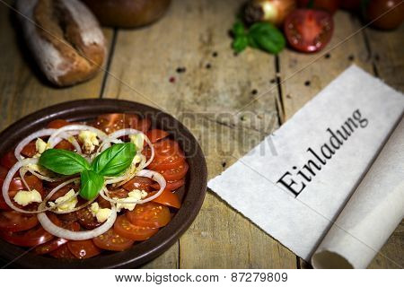 Tomato And Onion Salad On A Old Wooden Table, Scroll With Word Einladung