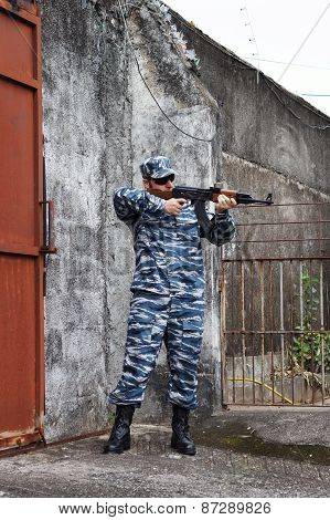 Caucasian Man With Black Sunglasses In Urban Warfare Holding Rifle