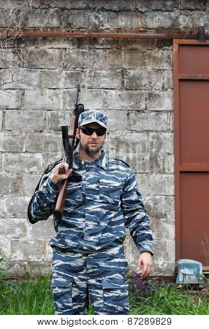 Caucasian Military Man With Black Sunglasses In Urban Warfare Holding Rifle On Shoulder