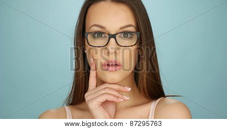 Serious attractive thoughtful young woman wearing glasses staring off to the right of the frame with her hand to her chin, closeup of her face