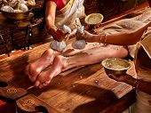 Young woman having feet Ayurveda India spa massage. poster