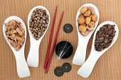 Acupuncture needles and chinese herbal medicine selection with chopsticks and I ching coins over bamboo background. poster