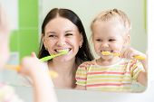 Mom with child look at reflection in mirror brushing teeth at bathroom poster