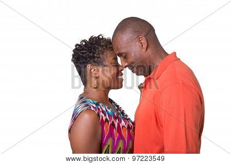 Portrait of an older couple standing close and looking at each other isolated