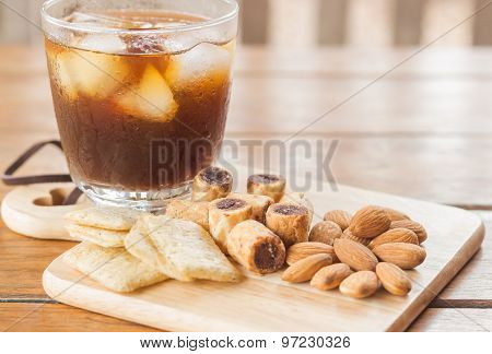 Glass Of Black Iced Coffee With Some Snack