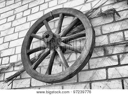 Antique Wooden Wagon Wheel Hanging On A Brick Wall.