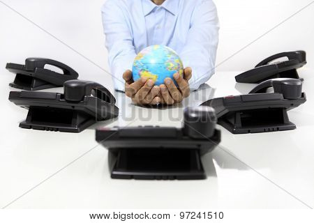 Hands Globe With Office Phones On Desk, Global International Support Concept