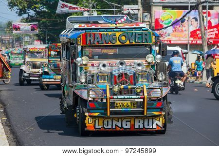 Jeepneys passing Filipino inexpensive bus service.