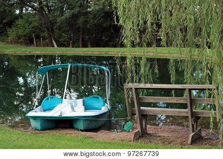 Pedal boat sitting on bank near bench