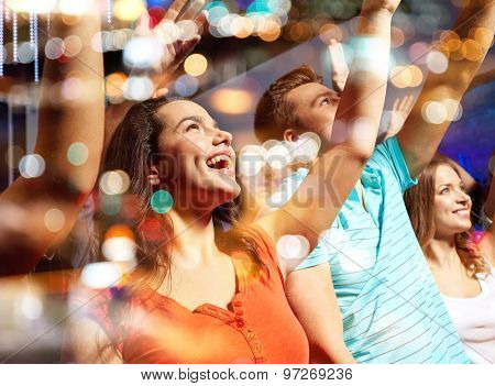 party, holidays, celebration, nightlife and people concept - smiling friends waving hands at concert in club poster