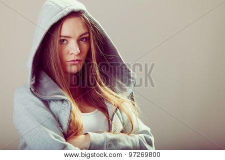 Pensive Teenager Girl In Hood Crossing Arms.