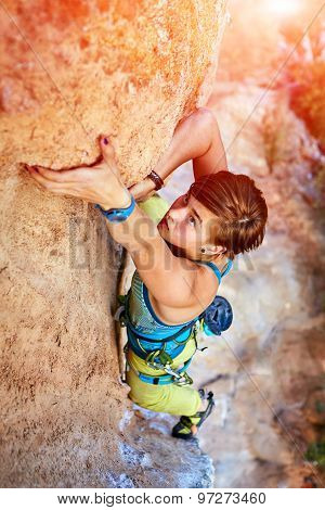 female rock climber climbs on a rocky wall poster