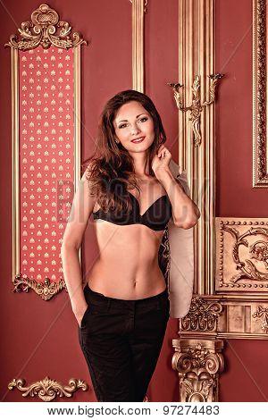 Beautiful Sexy Girl Stands Near A Maroon Wall. Girl In Black Bra