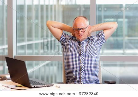 middle age balding man with pain in the neck stretching arms in his office