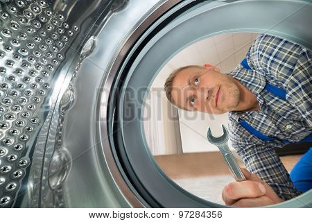 Repairman Looking Inside The Washing Machine