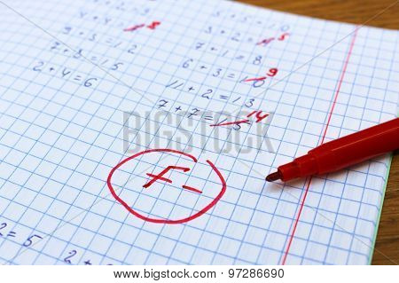 Errors corrected in red pen in a notebook. Bad score for the solution of mathematical expressions. M