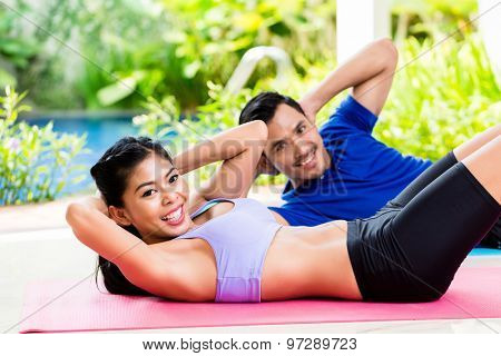 Asian fitness couple, man and woman, doing sit-up in tropical home