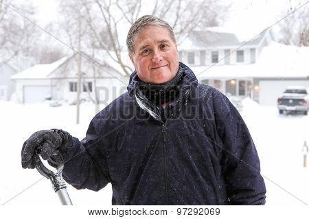 Smiling older man shoveling snow in winter.