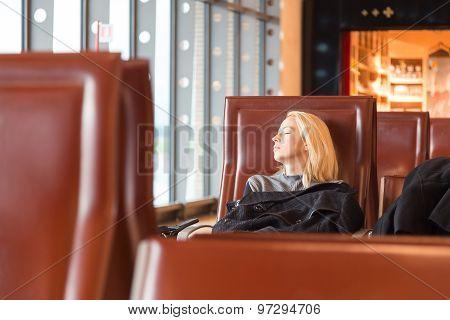 Tired female traveler waiting for departure.