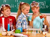 Happy child holding flask in chemistry class. poster