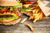 Delicious hamburger and french fries on wooden background poster