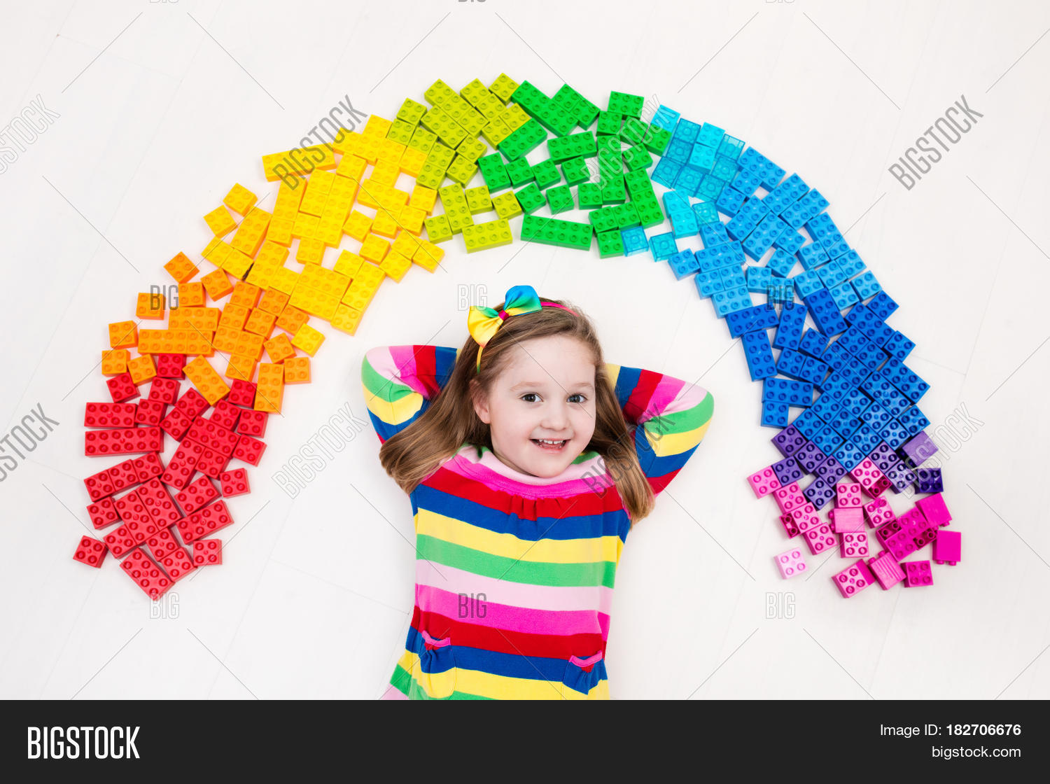 8dbae1fd9f1e Funny little girl playing with colorful rainbow plastic blocks. Kids play  create and learn colors