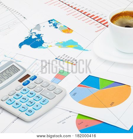 Close Up Studio Shot Of A Coffee Cup And A Calculator Over Some Charts