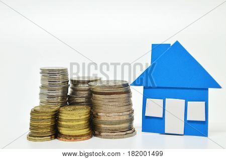 Blue paper house model and stacks of coins