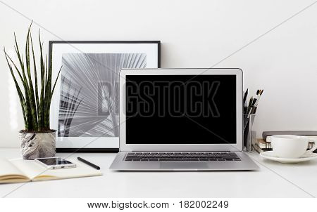 Creative designer desktop with blank copy screen laptop bw photo in a frame smartphone stationery green plant in a pot cup of coffee on white wall background. Stylish hipster workspace mock up poster