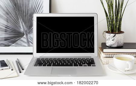 Front view of creative hipster desktop with blank copy space laptop computer mobile phone on the notepad shot of a palm leaf on background stationery and decorative plant on stack of books. Mock up