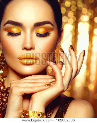 Gold Woman skin. Beauty fashion model girl with Golden make up, hair and jewellery on black background. Gold earrings, and necklace. Glance Fashion art portrait, manicure and make up