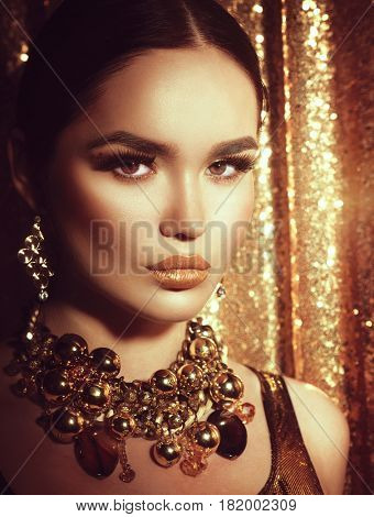 Beauty glamour lady. Beauty fashion model girl with Golden make up, hair and jewellery on gold blinking background. Gold earrings, and necklace. Fashion Woman portrait, Hairstyle and make up